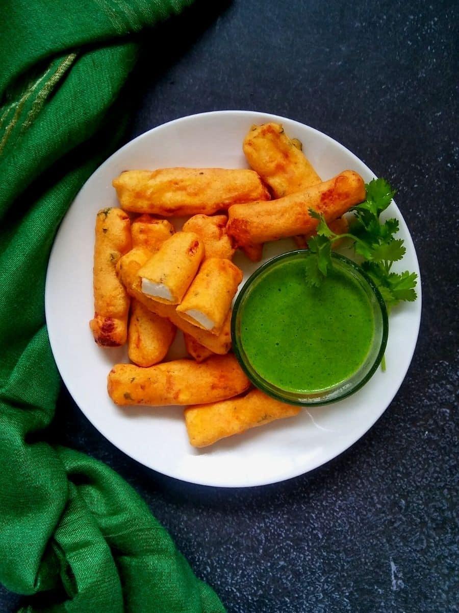 Punjabi paneer pakora on a white plate with green chutney