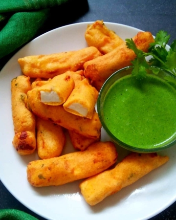 paneer pakora on a white plate with green chutney in a bowl