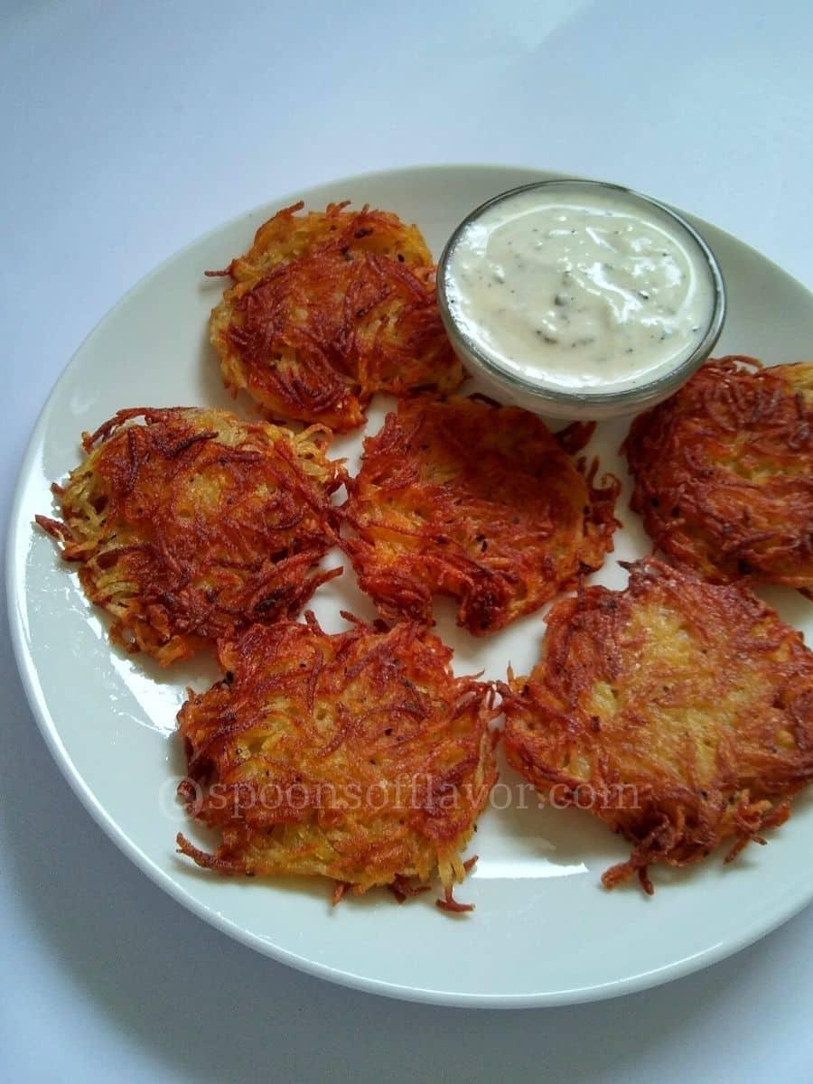 Crispy potato fritters served on a white plate with yogurt sauce